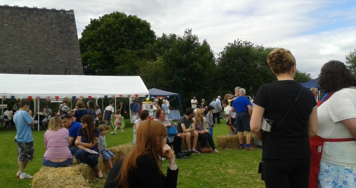 People sitting on hay bales at the village fete in Lach Dennis